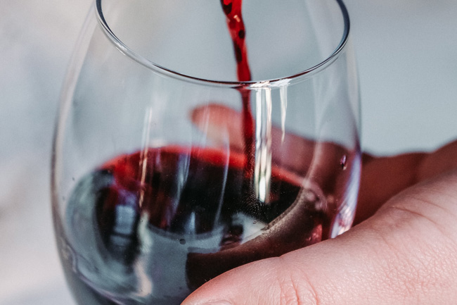 Person pouring glass of red wine