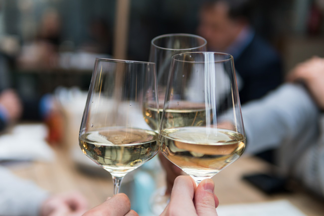 Cheers with three glasses of white wine