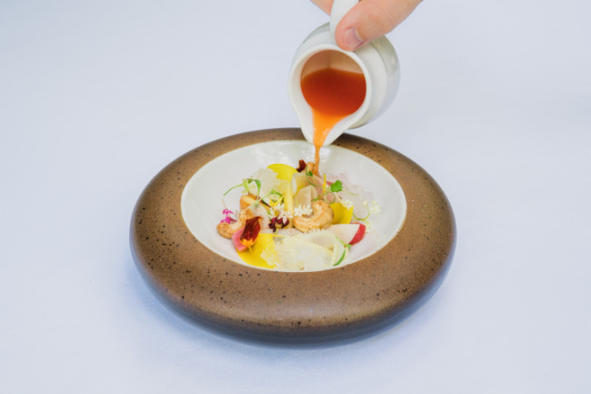 Hand pouring sauce into round plate filled with vegetables, fruit and edible flowers