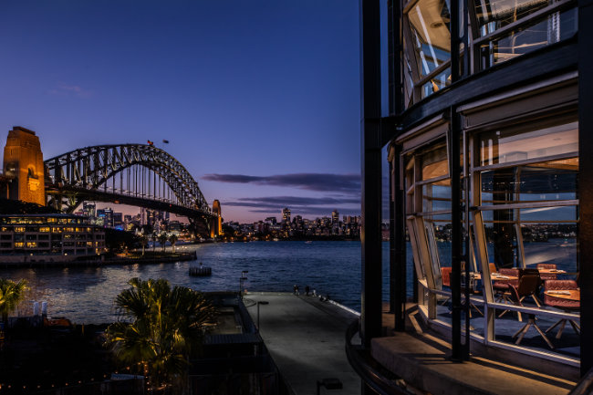 Outside view of a restaurant overlooking the Sydney Harbour Bridge at night time