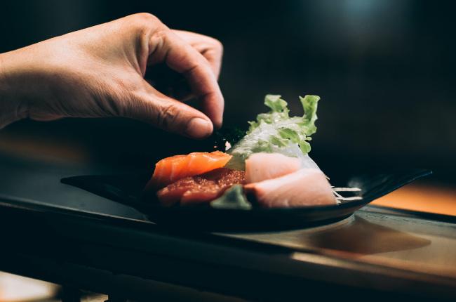 someone garnishing a plate of sushimi