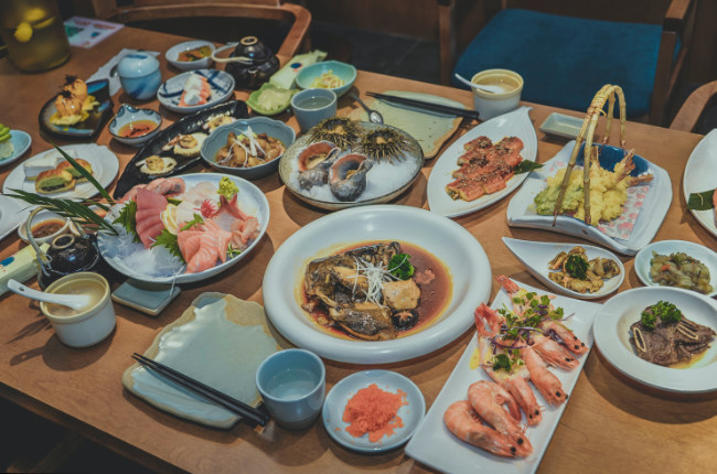a selection of Japanese dishes laid out on a restaurant table