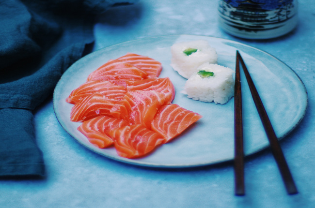 sliced salmon sashimi with a side of rice