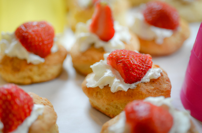 a selection of strawberry muffins resting on a dollop of fresh cream