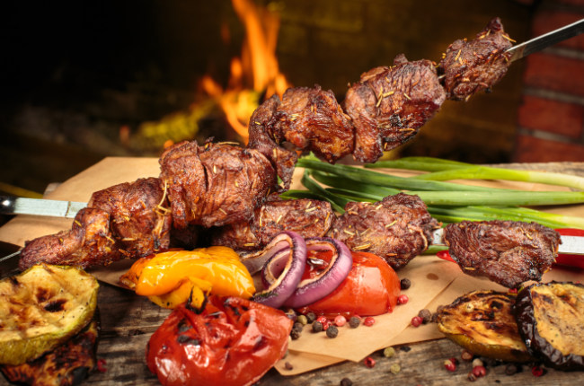 delicious meat on a skewer with fire in the background
