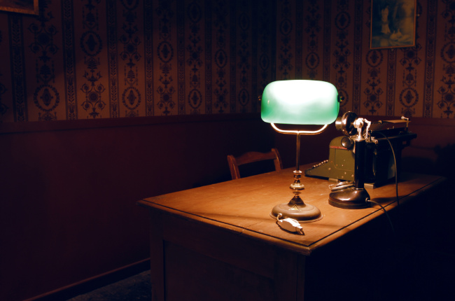 a lamp on an old desk in a dark puzzle room