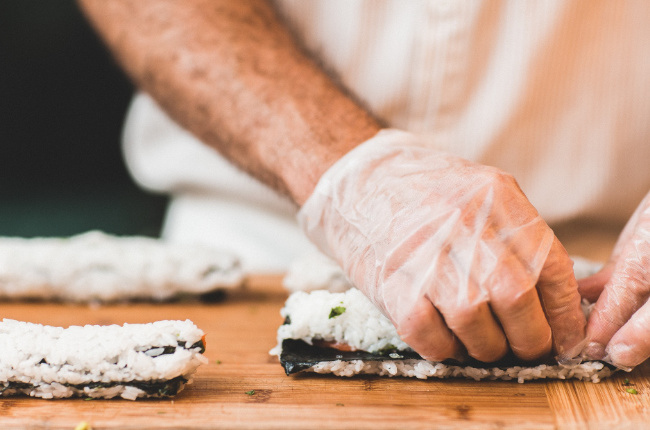 a sushi master preparing a roll of sushi