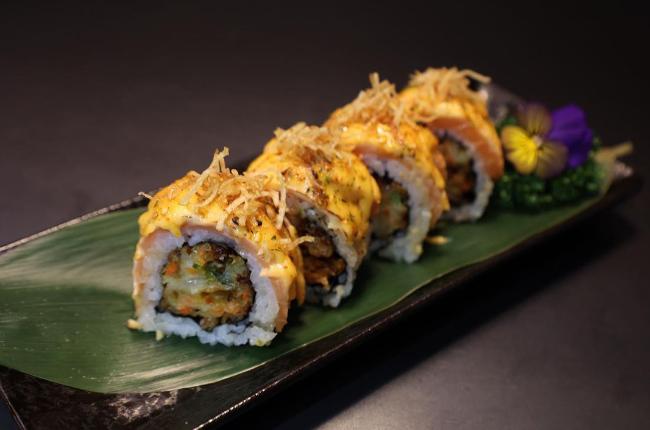 tempura fried sushi resting on a banana leaf
