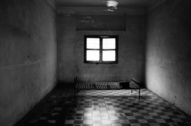a dark prison cell with a bed in the middle of the room