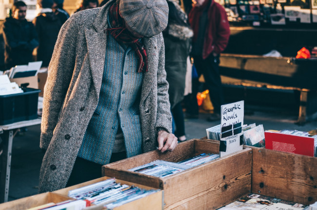 man looking through a collection of novels