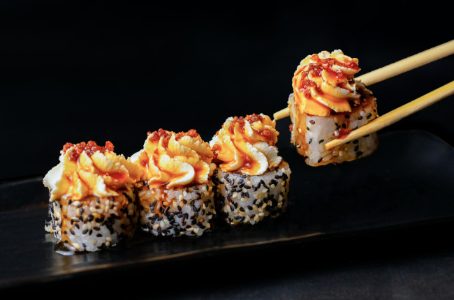 sushi topped with whipped cream cheese and spicy sauce